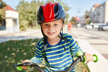 Boy in helmet standing with bike at autumn park