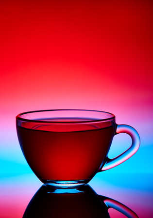 Two cups and saucers of glass. Tea is poured into the top Cup. Helium filter gives a beautiful light. Stock Photo