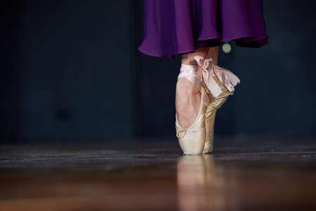 Ballerina legs in pointes on dark background