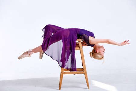 Young female dancer practicing in a beautiful pose, lying on chair. Side view