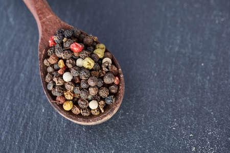 Chinesischer Pfeffer, Sichuan-Pfeffer im hölzernen Löffel auf schwarzer Schiefersteinplatte