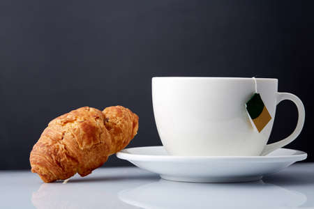 Breakfast with te and croissants on grey background, close-up