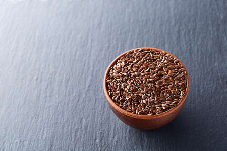 Many flax seeds are scattered in the background, and poured into a clay plate, space for text