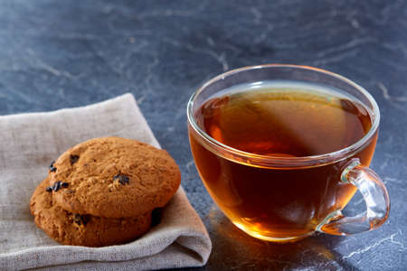 Shallow depth of field photo of a glass cup of black tea with brownies on a dark greyish marble background.