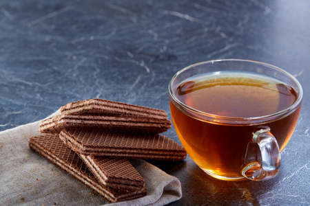 A glass cup of black tea with waffles on a dark greyish marble background. Breakfast background Stock Photo