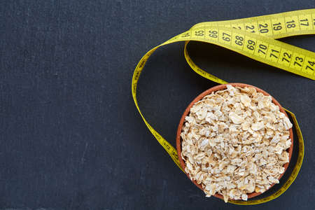 Top view picture of a bowl of oatmeal with flexible ruler isolated on dark background, close-up. Stock Photo