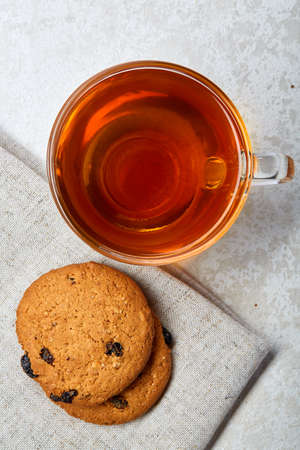 Top view close up vertical picture of earl grey or black tea in transparent glass cup with chocolate chips cookies on a cotton napkin on white background. Delicious dessert and refreshing teatime. Breakfast background.