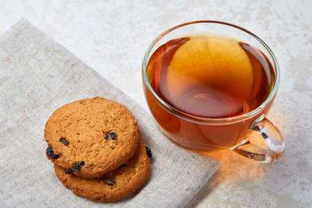 Top view close up picture of earl grey or black tea in transparent glass cup with cookies pieces next to a cotton napkin on white background, selective focus. Delicious dessert and refreshing teatime. Breakfast background.