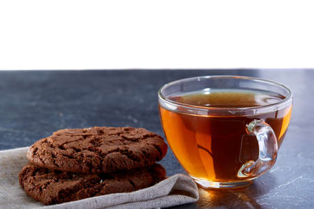 A transparent glass cup of black tea with cookies on a dark greyish marble background. Breakfast background