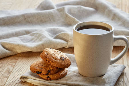 White porcelain cup of earl grey or black tea with chocolate chips cookies decorated with light cotton napkin on a rustic wooden background, top view, selective focus