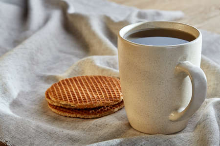 White porcelain cup of earl grey or black tea with wafflesdecorated with light cotton napkin on a rustic wooden background, top view, selective focus, vertical. Stock Photo