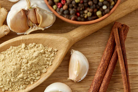 Composition of powder spices on spoon, yellow, red and black peppercorn in ceramic bowl and garlic, ginger, cinnamon, clove and bay leaf on rustic wooden table background, close-up, top view, selective focus, shallow depth of field. Stock Photo