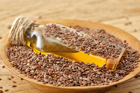 Linseed oil in a glass bottle in the clay ceramic plate full of raw flax seeds on a brown rustic wooden table background, top view, close-up, shallow depth of field, selective focus, front focus. Healthy lifestyle concept.