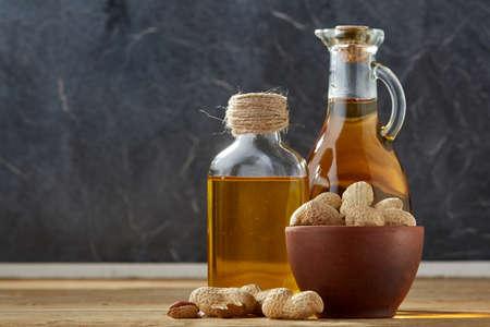 Composición de aceite aromático en un frasco de vidrio y una botella con cacahuetes sin pelar en un recipiente en la mesa de madera sobre un fondo de mármol oscuro, primer plano, vertical. Alimento terapéutico nutritivo para un estilo de vida saludable.