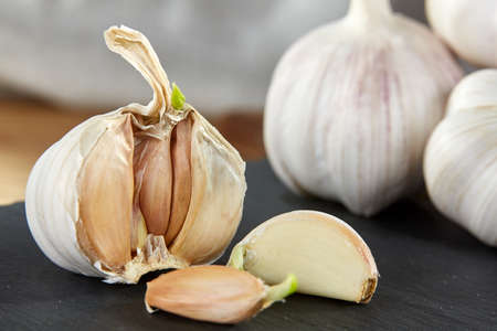 Garlic on flat wooden plate put on black piece of board on rustic wooden background. Close-up, shallow depth of field, selective focus, front focus, macro. Healthy lifestyle concept.