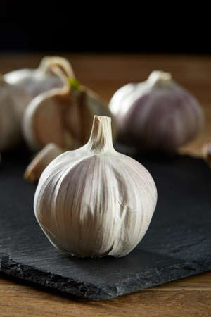 Garlic on flat black piece of board. Close-up, shallow depth of field, selective focus, front focus, macro. Aromatic and gourmet combination of garlic bulbs. Heart diseases prevention. Healthy lifestyle concept. Stock Photo