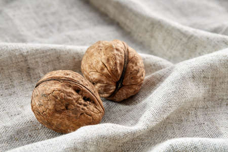 A stack of hard shells of walnuts piled together on light grey fabric cotton tablecloth, copy space, shallow depth of field, selective focus, front focus, macro. Nutritious food. Healthy lifestyle concept. Imagens