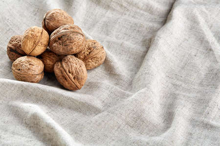 A stack of hard shells of walnuts piled together on light grey fabric cotton tablecloth, copy space, shallow depth of field, selective focus, front focus, macro. Nutritious food. Healthy lifestyle concept. Banque d'images