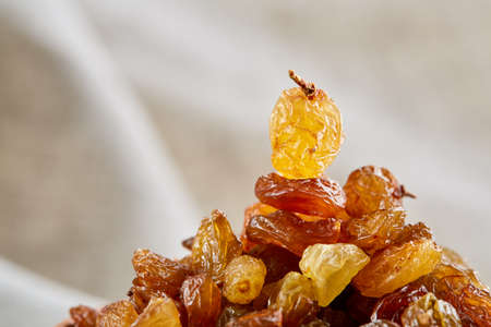 Dried raisins isolated on white background, close-up, macro, shallow depth of field, back light
