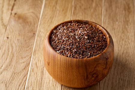 Flax seeds in wooden bowl on rustic wooden background, top view, shallow depth of field Banque d'images