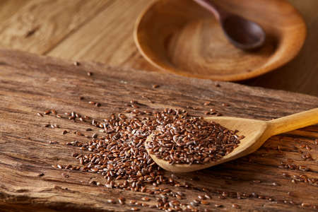Wooden spoon with flax seeds on rustic background, top view, close-up, shallow depth of field, selective focus Zdjęcie Seryjne