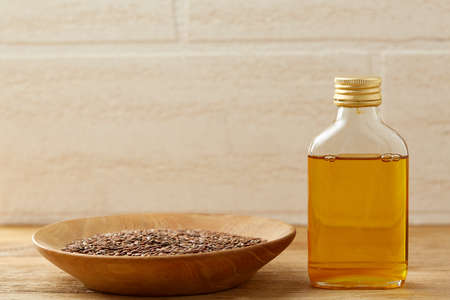 Flax seeds in bowl and flaxseed oil in glass bottle on wooden background, top view, close-up, selective focus