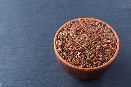 Close-up picture of flax seeds in a clay bowl isolated on dark background.