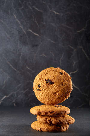 Lowkey picture of chocolate cookies on dark background, close-up, shallow depth of field, vertical