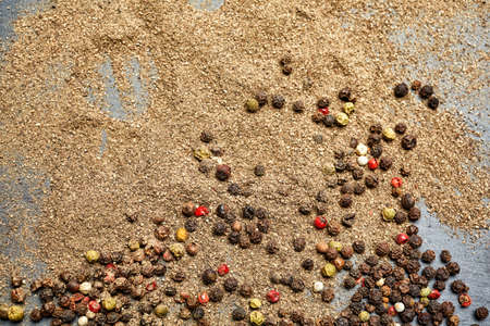 Mix of grind black pepper and black, white, red and yellow peppercorn. Selective focus.