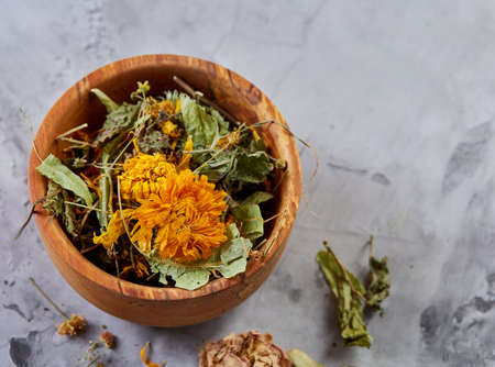 Spa still life with flowers in wooden bowl on light textured background, top view, close-up, selective focus. Alternative medicine. Spa natural concept. Dayspa cosmetics products. Spa and wellness setting. spa decoration concept