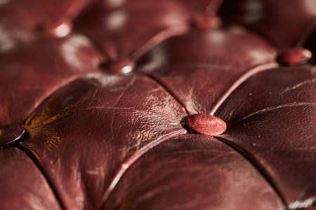 Dark brown leather buttoned background, close-up, shallow depth of field, selective focus. Luxurious interier. Vintage covering. Shining leather structure. Textured background.
