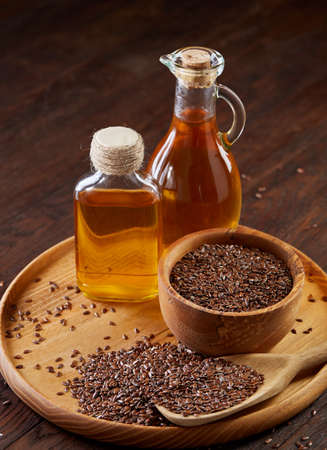 Brown flax seeds in wooden plate and flaxseed oil in glass bottle on brown rustic wooden background, top view, close-up, selective focus. Flax oil is rich in omega-3 fatty acid. Healthy lifestyle concept. Banque d'images