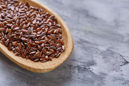 Flax seeds in wooden bowl and spoon on rustic wooden background, top view, shallow depth of field
