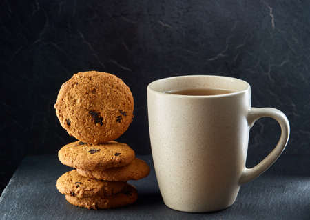 A glass cup of black tea with cookies on a dark greyish marble background. Breakfast background