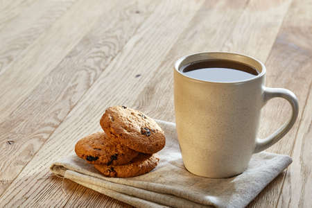 Porcelain teacup with chocolate chips cookies on cotton napkin on a rustic wooden background, top view Stock Photo
