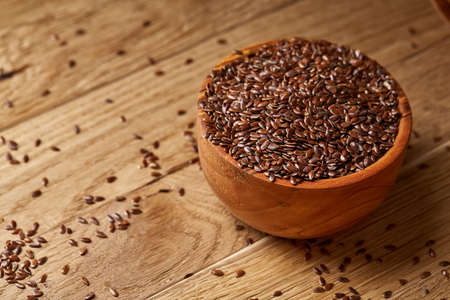 Wooden spoon with flax seeds on rustic background, top view, close-up, shallow depth of field, selective focus Standard-Bild