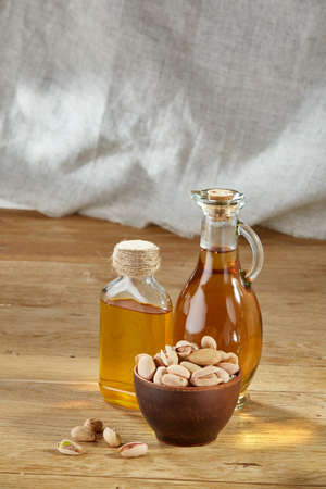 Aromatic oil in a glass jar and bottle with pistacios in bowl on wooden table, close-up, vertical.