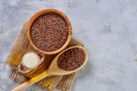 Flax seeds in bowl and flaxseed oil in glass bottle on light textured background, top view, close-up, selective focus
