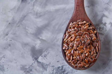 Wooden spoon with flax seeds on light textured background, top view, close-up, shallow depth of field, selective focus Banque d'images