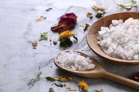 SPA concept: composition of spa treatment with natural sea salt, aromatic oil and flowers on white textured background, close up, top view, selective focus, shallow depth of field. Dayspa cosmetics products. Spa natural concept. Wellness setting. Stock Photo