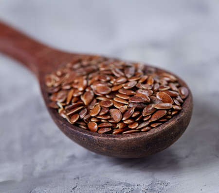 Wooden spoon with flax seeds on light textured background, top view, close-up, shallow depth of field, selective focus Imagens - 97182571