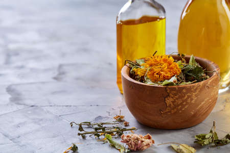Spa still life with flowers in bowl and oil jars on light textured background, top view, close-up, selective focus