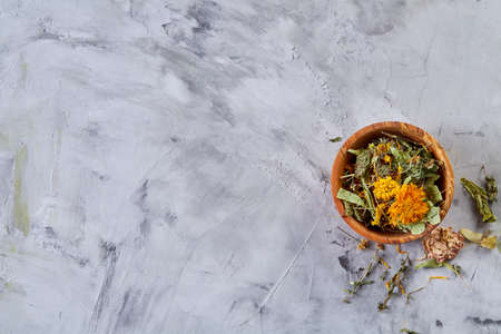 Spa still life with flowers in wooden bowl on light textured background, top view, close-up, selective focus