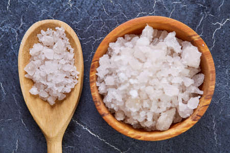 Large white sea salt in a natural wooden bowl on dark background, top view, close-up, selective focus Stock Photo