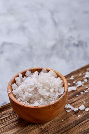 Large white sea salt in a natural wooden bowl on white background, top view, close-up, selective focus Stock Photo