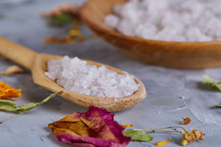 Composition of spa treatment on white background. Sea salt and flowers background, close up, top view, selective focus. Stock Photo