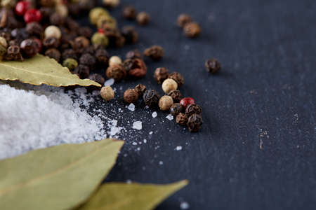Composition of bay laurel leaf with peppercorn and salt isolated on dark background, top view, close-up, selective focus