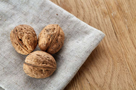 A stack of hard shells of walnuts piled together on light grey fabric cotton tablecloth, selective focus