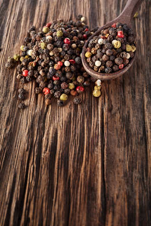 Top view on composition of peppercorn in wooden spoon on vintage wooden background, close-up, shallow depth of field