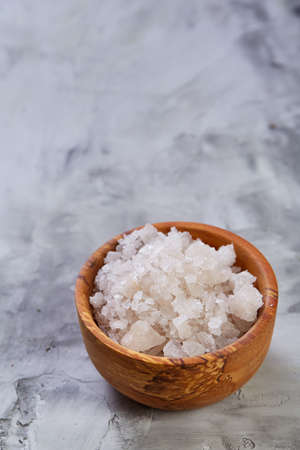 Large white sea salt in a natural wooden bowl on white background, top view, close-up, selective focus Reklamní fotografie